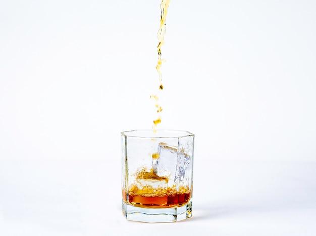 O copo de uísque com gelo frio no fundo branco