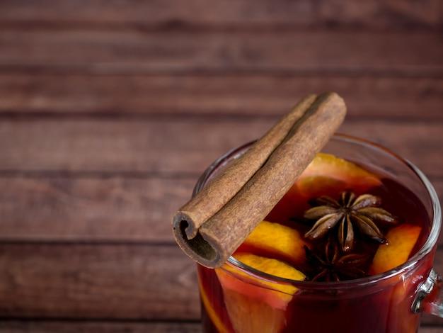 O copo de vidro de vinho tinto mulled o vinho em uma madeira com especiarias e laranja da canela.