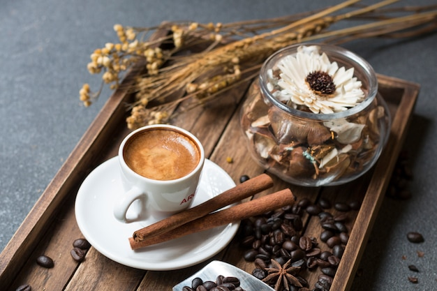 O copo do café, o feijão de café, a canela e as flores secadas rangem na bandeja de madeira.