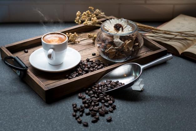 O copo do café, o feijão de café, o livro e as flores secadas rangem na bandeja de madeira com luz morna da manhã.