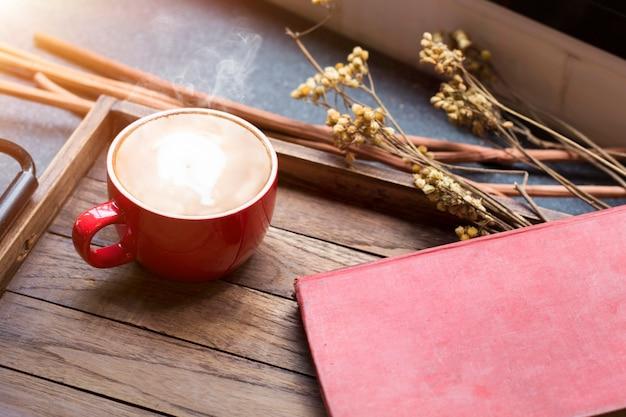O copo do café, o latte, o feijão de café e as flores secadas rangem em de madeira.