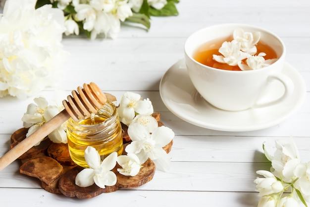 O copo do chá, derramando o mel de uma colher em um frasco, jasmim floresce em um fundo de madeira claro.