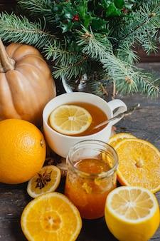 O copo do chá quente do limão com abóbora e gengibre alaranjados bloqueia em um fundo de madeira.
