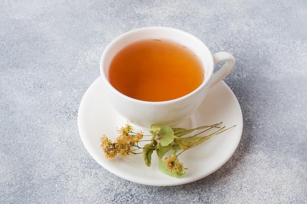 O copo do chá verde e as flores linden na superfície cinzenta. copie o espaço.