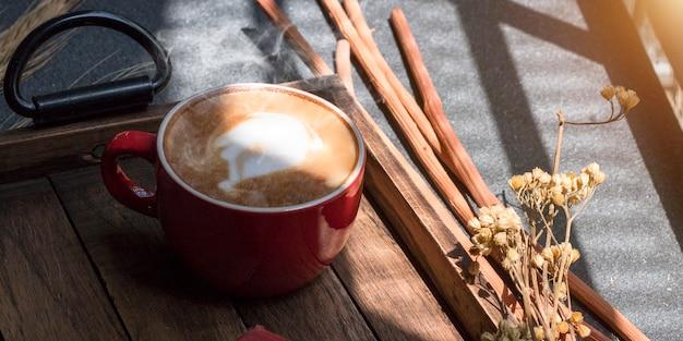 O copo do latte, o café e as flores secadas rangem em de madeira.