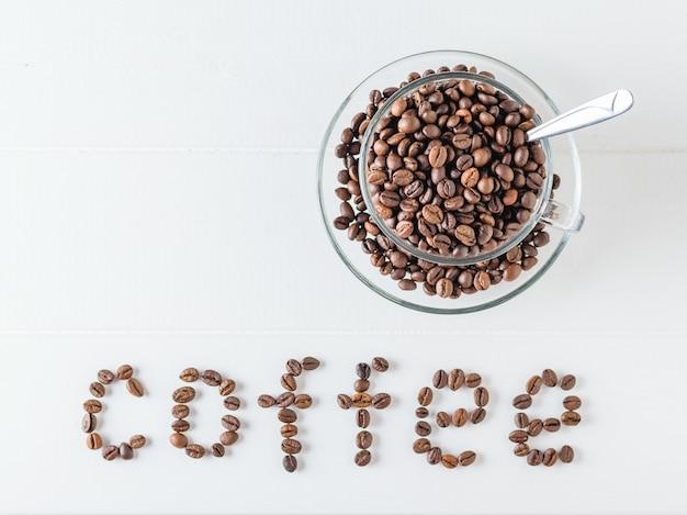 O copo e o saucer encheram-se com os feijões de café e a inscrição roasted do feijão de café em uma tabela de madeira branca.