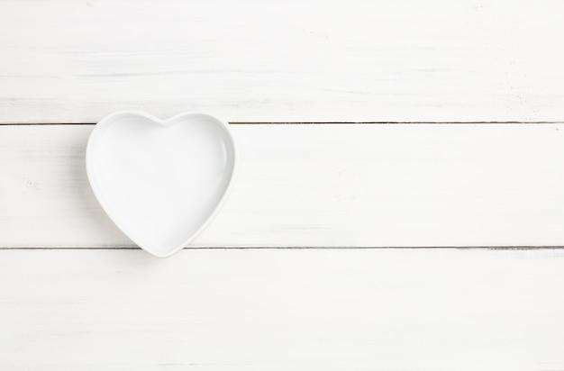 O copo ou a bacia esvaziam coração-dado forma na textura de madeira branca da prancha para o fundo. Foto Premium
