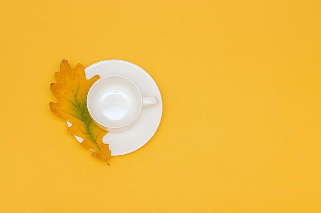 O copo vazio branco com pires e o carvalho do outono folheiam no fundo amarelo.