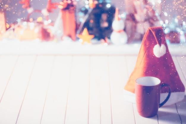 O copo vermelho na mesa de madeira na frente desfocou o fundo do objeto de natal