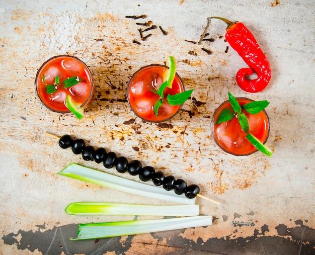 O coquetel bloody mary. coquetéis de tomate, álcool, gelo, limão, pimenta, sal e salgadinho com aipo e azeitonas pretas em mesa rústica. vista do topo