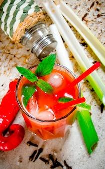 O coquetel bloody mary. coquetéis de tomate, vodka, gelo, limão, pimenta, sal e salgadinho com aipo em mesa rústica