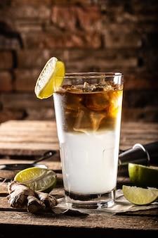 O coquetel highball dark n stormy servido como long drink com rum, suco de limão fresco e cerveja de gengibre.
