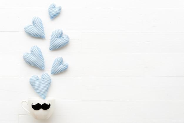 O coração azul handmade espirra para fora do copo de café no fundo branco da tabela.