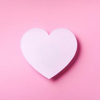 O coração branco cutted do papel sobre o fundo pastel punchy com espaço da cópia.