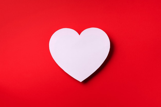 O coração branco cutted do papel sobre o fundo vermelho com espaço da cópia.