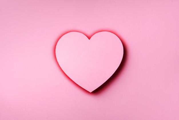 O coração cor-de-rosa cutted do papel sobre o fundo pastel punchy com espaço da cópia.