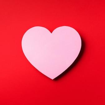 O coração cor-de-rosa cutted do papel sobre o fundo vermelho com espaço da cópia.