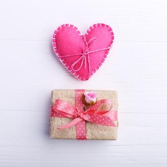 O coração de feltro do rosa e o presente feito a mão em uma tabela de madeira branca, conceito, bandeira, copiam o espaço.