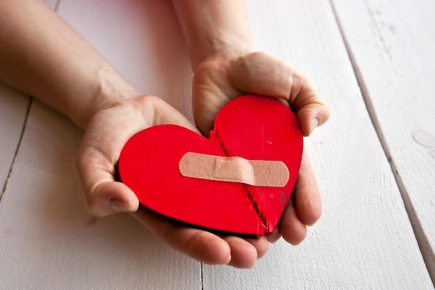O coração de madeira vermelho partido nas mãos de uma mulher