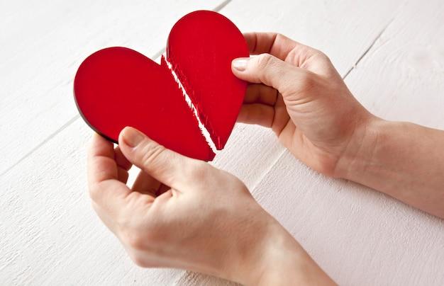 O coração de madeira vermelho quebrado nas mãos da mulher