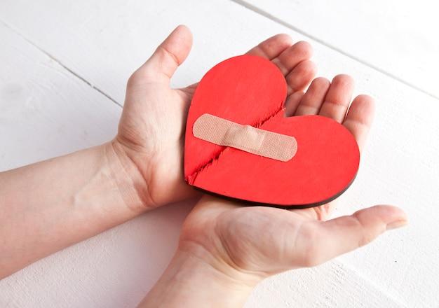 O coração de madeira vermelho quebrado nas mãos de uma mulher