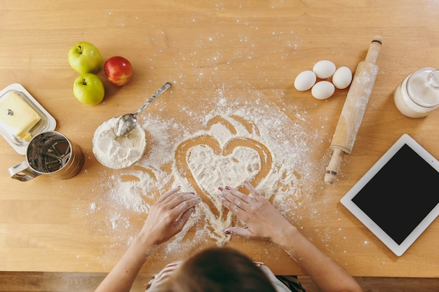 O coração desenhado de mão em farinha na mesa da cozinha e outros ingredientes e tablet. vista do topo.