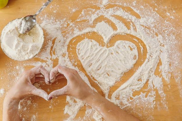O coração desenhado de mão em farinha na mesa da cozinha e outros ingredientes. vista do topo.