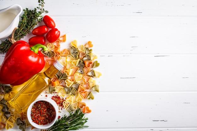O coração deu forma à massa com os ingredientes no fundo cinzento, vista superior. macarrão, creme, espinafre, tomate e ervas.