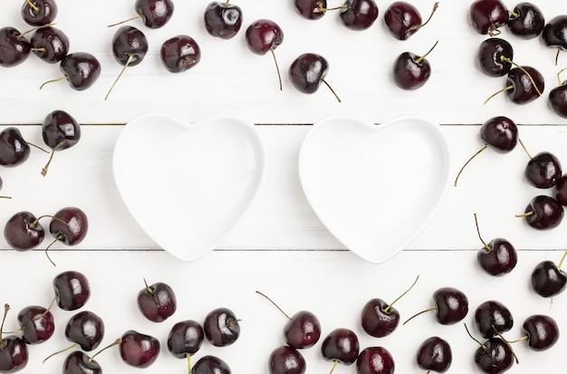 O coração deu forma aos copos cercados pelo montão de cerejas vermelhas e pretas maduras frescas na madeira branca.