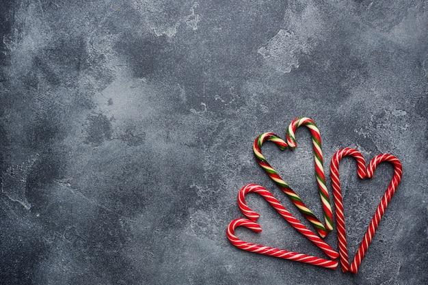O coração do bastão de doces do natal deu forma no cinza escuro com copyspace.