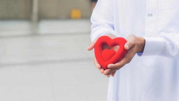 O coração do símbolo vermelho na mão do sacerdote ou a mão do homem.