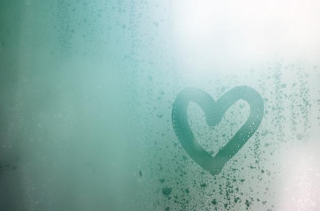 O coração é pintado no vidro embaçado no inverno