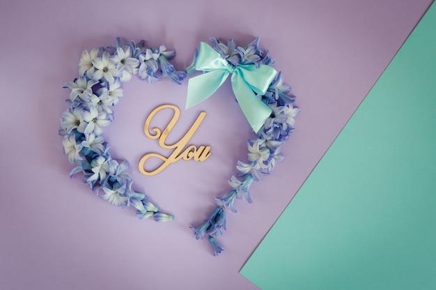 O coração feito das flores e da hortelã dos jacintos curva-se no fundo roxo.