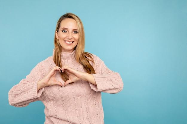 O coração fica seguro. jovem mulher sorridente no estúdio azul, posando para a câmera.