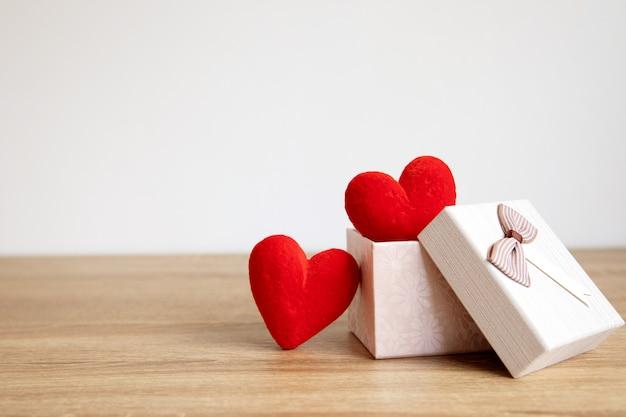 O coração vermelho dá forma na caixa de presente na madeira