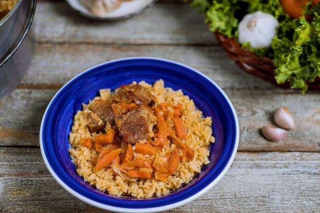 O cordeiro do pilaf de samarkand, arroz, cebola, cenouras amarelas, especiarias vegetais apresenta no prato nacional do uzbeque.