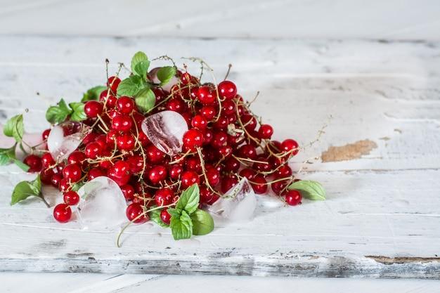 O corinto vermelho com gelo e verde sae na madeira branca. ainda vida de comida.