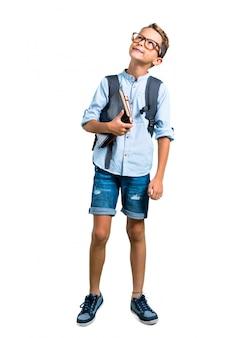 O corpo cheio do menino do estudante com trouxa e os vidros estão e olhando acima. de volta à escola