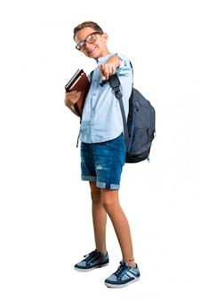 O corpo cheio do menino do estudante com trouxa e vidros aponta o dedo em você. de volta à escola