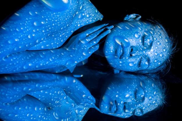 O corpo da mulher com padrão azul e seu reflexo