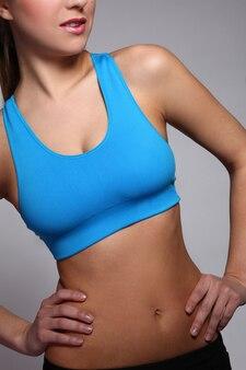 O corpo da mulher em um desgaste de fitness