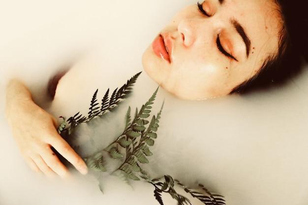 O corpo da mulher submerso na água segurando a planta verde