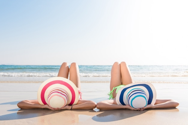 O corpo de biquíni sexy das mulheres asiáticas goza do mar, deitando na areia da praia com um chapéu de chapelaria e ambas as pernas no ar. estilo de vida feliz da ilha. areia branca e mar cristalino de praia tropical.