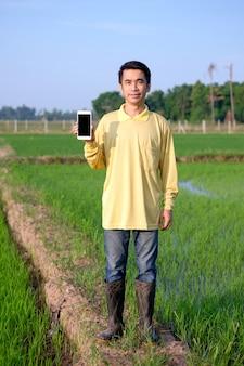 O corpo inteiro de um agricultor asiático usa uma camisa amarela segurando um smartphone