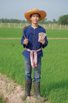 O corpo inteiro de um fazendeiro asiático usa um traje tradicional, sorrindo e segurando o dinheiro das notas tailandesas na fazenda verde