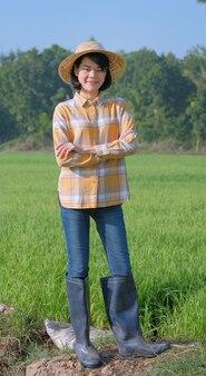 O corpo inteiro de uma mulher agricultora asiática usa uma camisa amarela em pé e os braços cruzados na fazenda