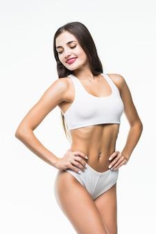 O corpo magro da mulher bronzeada isolado sobre a parede branca.