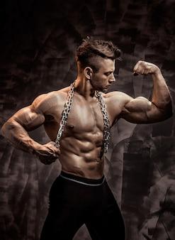 O corpo masculino perfeito - incrível fisiculturista posando. segure uma corrente com tatuagem