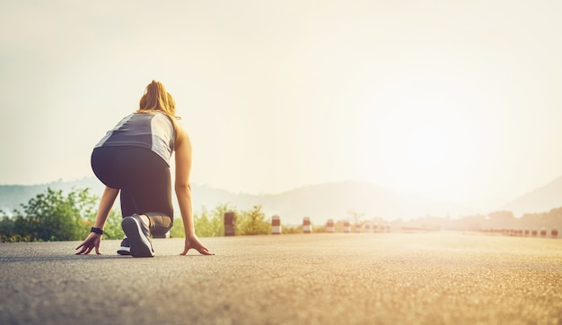 O corredor da mulher nos calçados da estrada está preparado para deixar o ponto de partida.