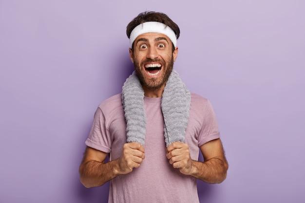 O corredor masculino feliz sorri amplamente, surpreso por cobrir uma longa distância na maratona